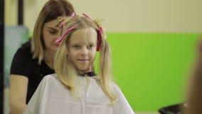 Πορτρέτο του χαριτωμένου μικρού κοριτσιού hairdressing στο σαλόνι απόθεμα βίντεο