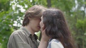 Πορτρέτο του χαριτωμένου νέου ζεύγους που φιλά tenderly κοντά επάνω Ευτυχής χρόνος εξόδων κοριτσιών και αγοριών μαζί στο πάρκο le απόθεμα βίντεο