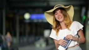 Πορτρέτο του χαριτωμένου νέου κοριτσιού στο θερινό καπέλο που κρατά το διαβατήριο και το εισιτήριό της στον αερολιμένα Διακινούμε απόθεμα βίντεο