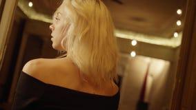 Πορτρέτο του χαριτωμένου ξανθού κοριτσιού από την πίσω πλευρά που φορά το όμορφο μαύρο φόρεμα απόθεμα βίντεο