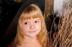 πορτρέτο του χαριτωμένου ξανθού κοριτσιού στο μαύρο καπέλο στοκ εικόνα