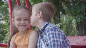 Πορτρέτο του χαριτωμένου ξανθού μάγουλου φιλήματος αγοριών μιας όμορφης συνεδρίασης κοριτσιών στην ταλάντευση στην παιδική χαρά Τ φιλμ μικρού μήκους