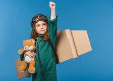 πορτρέτο του χαριτωμένου παιδιού στο πειραματικό κοστούμι με τη teddy αρκούδα και τα χειροποίητα φτερά αεροπλάνων εγγράφου Στοκ εικόνα με δικαίωμα ελεύθερης χρήσης