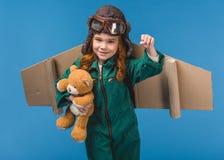 πορτρέτο του χαριτωμένου παιδιού στο πειραματικό κοστούμι με τη teddy αρκούδα και τα χειροποίητα φτερά αεροπλάνων εγγράφου Στοκ Εικόνες
