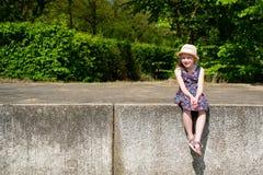 Πορτρέτο του χαριτωμένου χαμογελώντας κοριτσιού που φορά τη συνεδρίαση καπέλων στο διατηρώντας τοίχο στοκ φωτογραφία με δικαίωμα ελεύθερης χρήσης