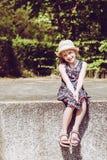 Πορτρέτο του χαριτωμένου χαμογελώντας κοριτσιού που φορά τη συνεδρίαση καπέλων στο διατηρώντας τοίχο στοκ εικόνα με δικαίωμα ελεύθερης χρήσης