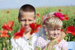 Πορτρέτο του χαριτωμένων αδελφού και της αδελφής στο πεδίο παπαρουνών Στοκ Εικόνες