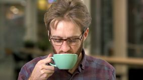 Πορτρέτο του χαρούμενου γενειοφόρου ατόμου στα γυαλιά που πίνει τον καφέ κοντά επάνω Τα μάτια clos Beardie απολαμβάνουν το ποτό τ απόθεμα βίντεο