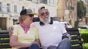 Πορτρέτο του χαρούμενου μοντέρνου ηλικιωμένου ανθρώπου που χαλαρώνει στον πάγκο στην πόλη απόθεμα βίντεο