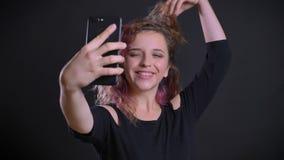 Πορτρέτο του χαρούμενου νέου καυκάσιου κοριτσιού με τη ρόδινη τρίχα που κάνει τις selfie-φωτογραφίες που χρησιμοποιούν το smartph φιλμ μικρού μήκους