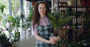 Πορτρέτο του όμορφου ανθοκόμου γυναικών που στέκεται στο ανθοπωλείο με τις εξωτικές εγκαταστάσεις