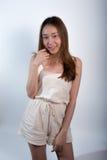 Πορτρέτο του όμορφου ασιατικού κοριτσιού που φορά τα σορτς γήινου τόνου στάση στο άσπρο υπόβαθρο Προκλητικός τρίχωμα μακρύ χαμόγε Στοκ φωτογραφία με δικαίωμα ελεύθερης χρήσης