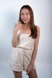 Πορτρέτο του όμορφου ασιατικού κοριτσιού που φορά τα σορτς γήινου τόνου στάση στο άσπρο υπόβαθρο Προκλητικός τρίχωμα μακρύ χαμόγε Στοκ Εικόνες