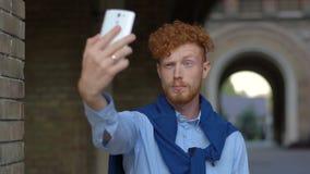 Πορτρέτο του όμορφου ατόμου με την κόκκινη σγουρή τρίχα και της γενειάδας που κάνει τα αστεία πρόσωπα παίρνοντας selfies μέσω του απόθεμα βίντεο