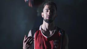 Πορτρέτο του όμορφου βέβαιου παίχτης μπάσκετ που παίζουν με τη σφαίρα στα ισχυρά χέρια με τη δερματοστιξία φιλμ μικρού μήκους