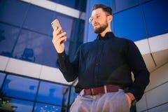 Πορτρέτο του όμορφου γενειοφόρου επιχειρηματία που εξετάζει το τηλέφωνο κυττάρων που στέκεται κοντά στο γραφείο Στοκ Φωτογραφία