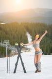 Πορτρέτο του όμορφου γυμνού θηλυκού σκιέρ με τα σκι Η χαμογελώντας γυναίκα παρουσιάζει αντίχειρες στη χιονώδη κλίση Στοκ Φωτογραφία