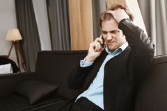 Πορτρέτο του όμορφου δυστυχισμένου γενειοφόρου ατόμου με την ξανθή τρίχα που μιλά στο τηλέφωνο και που ανατρέπεται για τα προβλήμ Στοκ Φωτογραφίες