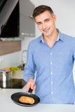 Πορτρέτο του όμορφου εύθυμου ατόμου που κατασκευάζει τις τηγανίτες Στοκ εικόνες με δικαίωμα ελεύθερης χρήσης