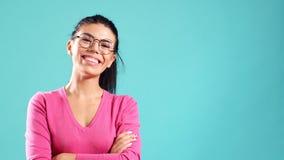 Πορτρέτο του όμορφου εύθυμου κοριτσιού με το μακροχρόνιο μαύρο χαμόγελο τρίχας που εξετάζει τη κάμερα πέρα από το μπλε υπόβαθρο απόθεμα βίντεο
