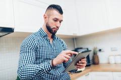 Πορτρέτο του όμορφου, ελκυστικού ατόμου που φαίνεται συνταγές στο διαδίκτυο Άτομο που χρησιμοποιεί τη νέα τεχνολογία, που λειτουρ Στοκ Εικόνες