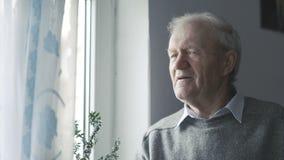 Πορτρέτο του όμορφου ηληκιωμένου που εξετάζει τα παράθυρα και που χαμογελά στη κάμερα 4K απόθεμα βίντεο