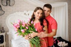Πορτρέτο του όμορφου και νέου ζεύγους με τη μεγάλη ανθοδέσμη των ρόδινων τουλιπών Στοκ εικόνες με δικαίωμα ελεύθερης χρήσης