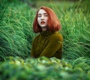 Πορτρέτο του όμορφου κοκκινομάλλους κοριτσιού στην ψηλή χλόη σε ένα θερμό sw στοκ εικόνες με δικαίωμα ελεύθερης χρήσης