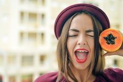 Πορτρέτο του όμορφου κομψού θηλυκού που φορά το κόκκινο μισό εκμετάλλευσης καπέλων πιλήματος papaya των φρούτων δίπλα στο πρόσωπό Στοκ Φωτογραφία