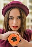 Πορτρέτο του όμορφου κομψού θηλυκού που φορά το κόκκινο μισό εκμετάλλευσης καπέλων πιλήματος papaya των φρούτων δίπλα στο πρόσωπό Στοκ φωτογραφία με δικαίωμα ελεύθερης χρήσης