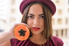 Πορτρέτο του όμορφου κομψού θηλυκού που φορά το κόκκινο μισό εκμετάλλευσης καπέλων πιλήματος papaya των φρούτων δίπλα στο πρόσωπό Στοκ εικόνες με δικαίωμα ελεύθερης χρήσης