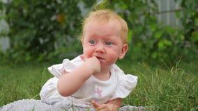 Πορτρέτο του όμορφου κοριτσάκι στην πράσινη χλόη Πρόσωπο του μικρού παιδιού με το δάχτυλο στο στόμα της Παιδί που βρίσκεται στην  απόθεμα βίντεο