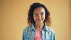 Πορτρέτο του όμορφου κοριτσιού αφροαμερικάνων που περπατά στο χαμόγελο καμερών απόθεμα βίντεο