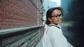 Πορτρέτο του όμορφου κοριτσιού αφροαμερικάνων που περπατά υπαίθρια έπειτα να εξετάσει τη κάμερα απόθεμα βίντεο