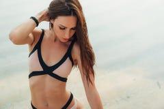 Πορτρέτο του όμορφου κοριτσιού με μακρυμάλλη στην τοποθέτηση μαγιό στην παραλία στοκ φωτογραφίες