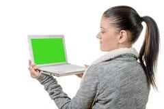 Πορτρέτο του όμορφου κοριτσιού που χρησιμοποιεί το lap-top με την πράσινη οθόνη Στοκ Φωτογραφία