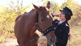 Πορτρέτο του όμορφου κοριτσιού στα ειδικά ενδύματα και του καπέλου με το καφετί άλογο το φθινόπωρο απόθεμα βίντεο