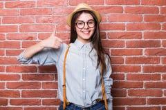 Πορτρέτο του όμορφου κοριτσιού στα περιστασιακά ενδύματα και του καπέλου που παρουσιάζει ΕΝΤΑΞΕΙ σημάδι Στοκ φωτογραφίες με δικαίωμα ελεύθερης χρήσης