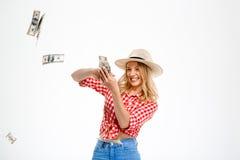 Πορτρέτο του όμορφου κοριτσιού χωρών που ρίχνει τα χρήματα πέρα από το άσπρο υπόβαθρο στοκ φωτογραφία