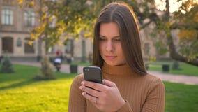 Πορτρέτο του όμορφου κοριτσιού brunette που τυλίγει την τροφή που χρησιμοποιεί το smartphone με τις διάφορες συγκινήσεις στο πράσ απόθεμα βίντεο