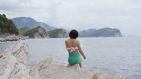 Πορτρέτο του όμορφου κοριτσιού brunette που φορά το καπέλο θερινού αχύρου και το μαγιό, κάθεται στους βράχους δίπλα στην αδριατικ απόθεμα βίντεο