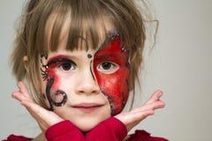 Πορτρέτο του όμορφου μικρού κοριτσιού με τη ζωγραφική πεταλούδων στο FA της στοκ εικόνα