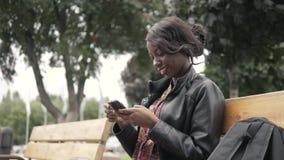 Πορτρέτο του όμορφου νέου αφρικανικού χαμόγελου γυναικών καθμένος έξω σε έναν πάγκο που κρατά το κινητό τηλέφωνο μετά από το πανε στοκ φωτογραφίες