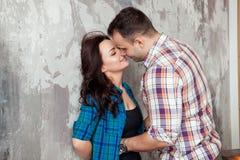 Πορτρέτο του όμορφου νέου ζεύγους στα περιστασιακά ενδύματα που αγκαλιάζουν και που χαμογελούν, που στέκεται ενάντια στον γκρίζο  Στοκ φωτογραφία με δικαίωμα ελεύθερης χρήσης