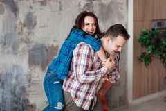 Πορτρέτο του όμορφου νέου ζεύγους στα περιστασιακά ενδύματα που αγκαλιάζουν και που χαμογελούν, που στέκεται ενάντια στον γκρίζο  Στοκ Φωτογραφία