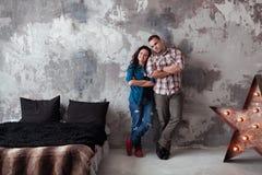 Πορτρέτο του όμορφου νέου ζεύγους στα περιστασιακά ενδύματα που αγκαλιάζουν και που χαμογελούν, που στέκεται ενάντια στον γκρίζο  Στοκ φωτογραφίες με δικαίωμα ελεύθερης χρήσης