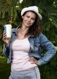Πορτρέτο του όμορφου νέου κοριτσιού στο καπέλο και του μοντέρνου σακακιού τζιν με το δροσερό ποτό με το άχυρο Στοκ εικόνες με δικαίωμα ελεύθερης χρήσης