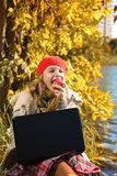 Πορτρέτο του όμορφου νέου κοριτσιού στο κόκκινο καπέλο που τρώει ένα μήλο και ένα χαμόγελο στοκ εικόνα