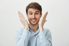 Πορτρέτο του όμορφου νέου συναισθήματος επιχειρηματιών που ανακουφίζεται και ευτυχούς, αυξάνοντας τους φοίνικες κοντά στο πρόσωπο στοκ φωτογραφία