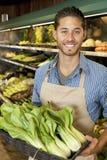 Πορτρέτο του όμορφου νέου υπαλλήλου πωλήσεων με το bok choy στην αγορά Στοκ Εικόνες